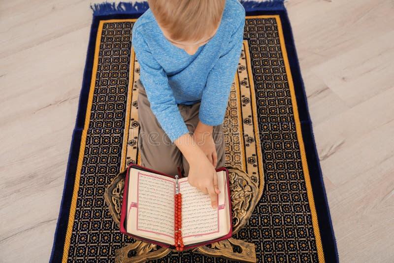 Mała Muzułmańska chłopiec czyta Koran na modlitewnym dywaniku obraz royalty free