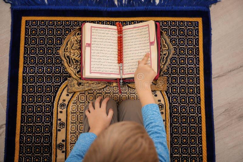 Mała Muzułmańska chłopiec czyta Koran na modlitewnym dywaniku fotografia royalty free