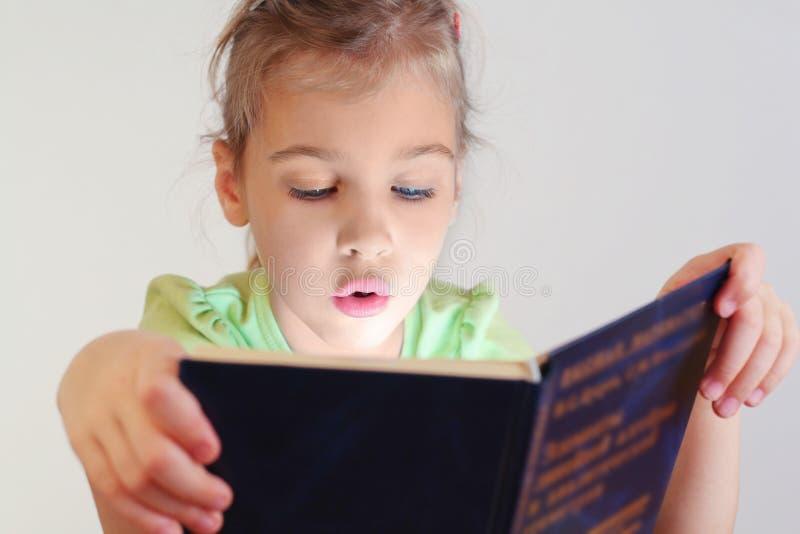 Mała niebieskich oczu dziewczyna czytająca błękitny książka obraz royalty free