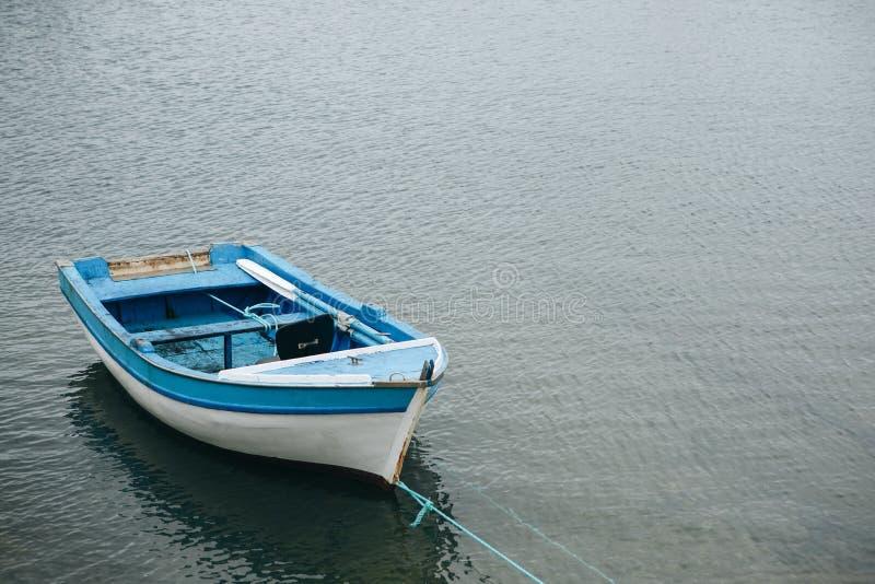 Mała osamotniona łódź rybacka na spokój wodzie obraz stock