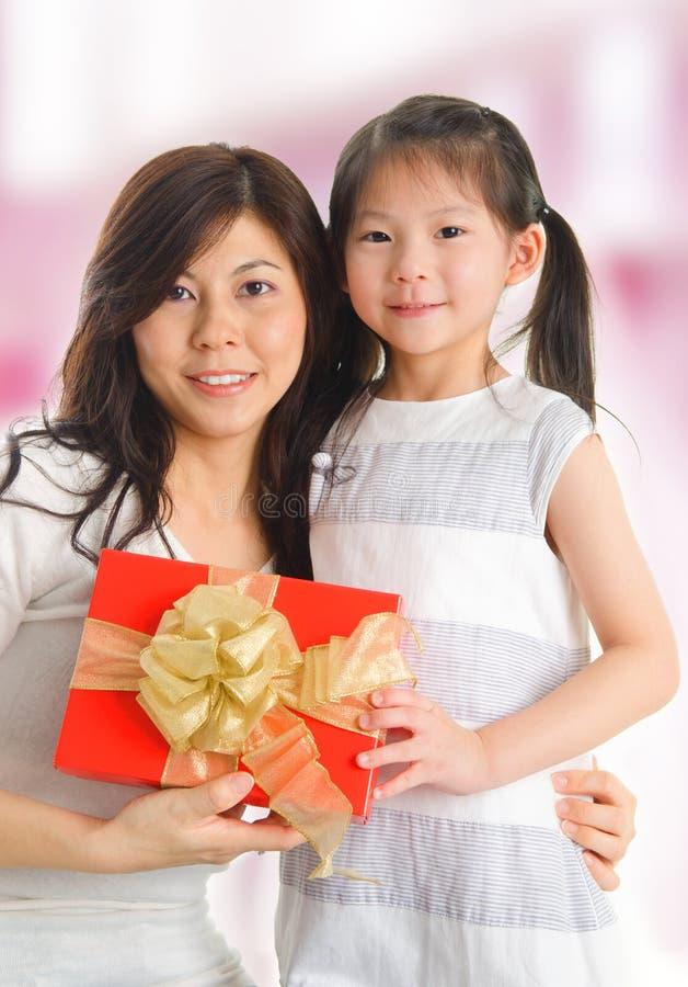 Azjatycka dziewczyna daje prezentowi jej szczęśliwa matka zdjęcia stock