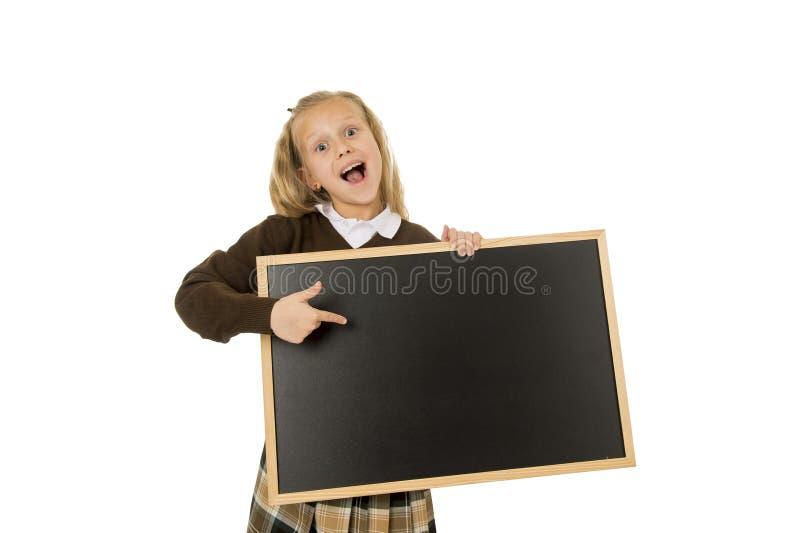 Mała piękna blond uczennica uśmiecha się mienia i seansu małego pustego blackboard szczęśliwego i rozochoconego obraz royalty free