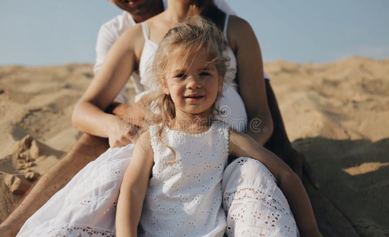 Mała piękna caucasian dziewczyny pozycja między ona rodzice iść na piechotę matka w ciąży Szczęśliwa rodzina w whote odziewa fotografia stock