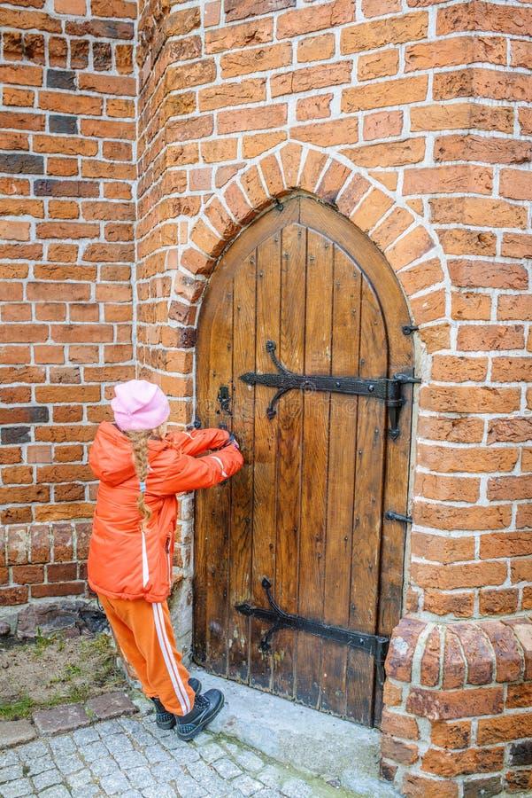 Mała piękna dziewczyna otwiera drzwi w fortecy obraz royalty free