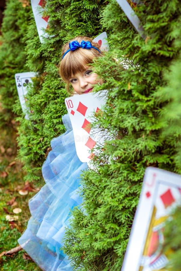 Mała piękna dziewczyna patrzeje spod jedlinowych drzew w długiej błękit sukni obraz royalty free