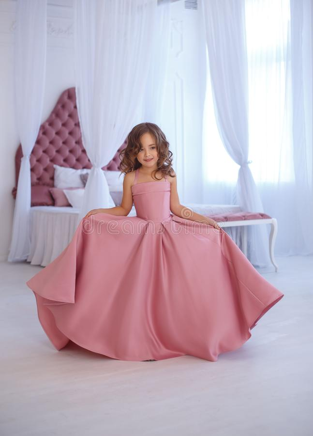 Mała, piękna dziewczyna w luksusowej menchii sukni, gaily okrąża w białym pokoju zdjęcie royalty free