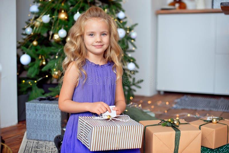 Mała piękna dziewczyna z blond kędzierzawym włosy rozważa jej prezenty przeciw tłu choinka Boże Narodzenia fotografia stock