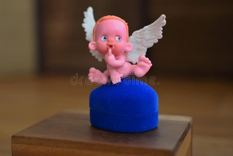 Mała postać anioła obsiadanie na biżuterii pudełku zamkniętym w górę lub blisko fotografia stock