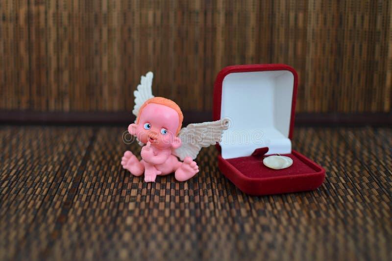 Mała postać anioła obsiadanie na biżuterii pudełku zamkniętym w górę lub blisko zdjęcie stock