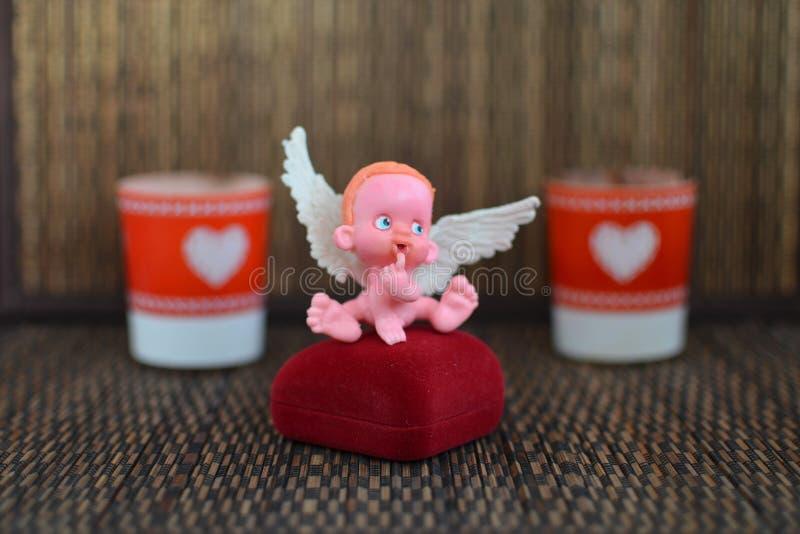 Mała postać anioła obsiadanie na biżuterii pudełku zamkniętym w górę lub blisko obrazy royalty free
