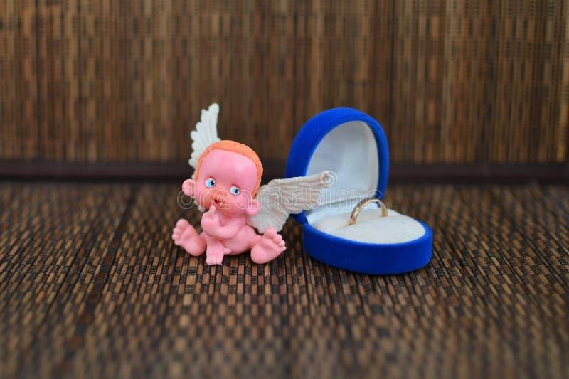 Mała postać anioła obsiadanie na biżuterii pudełku zamkniętym w górę lub blisko obraz stock