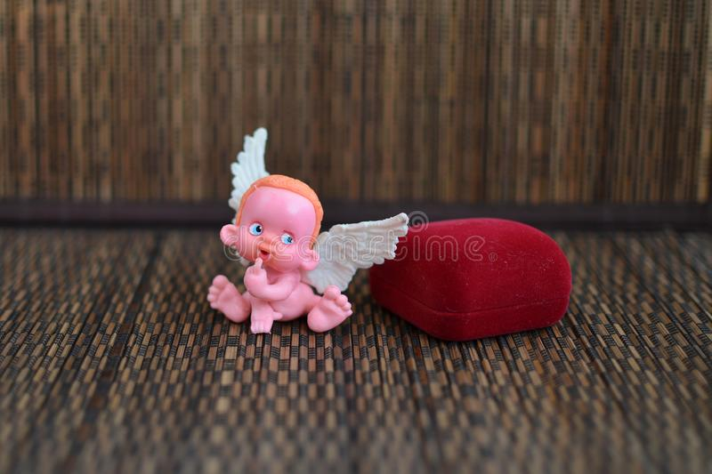 Mała postać anioła obsiadanie na biżuterii pudełku zamkniętym w górę lub blisko zdjęcia royalty free