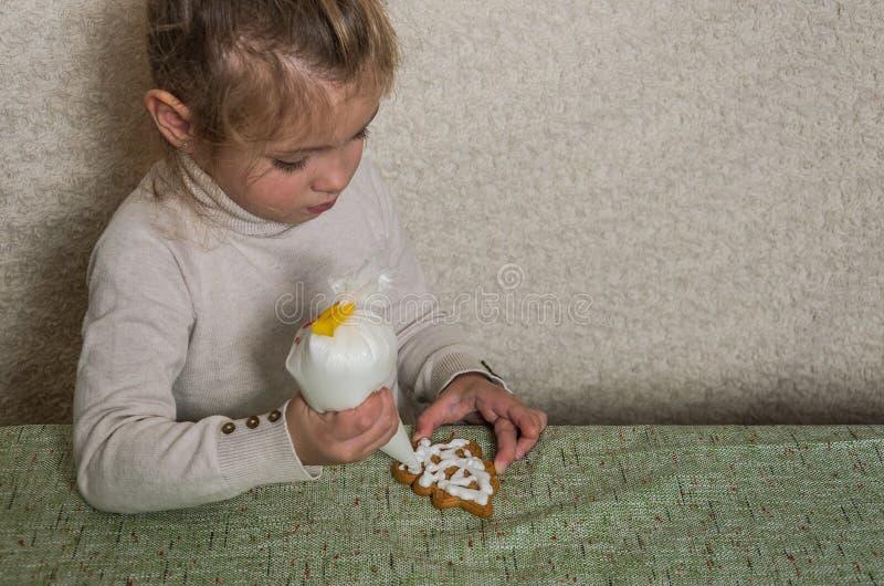 Mała powabna dziewczyna dekoruje nowego roku miodownika z białego cukieru lodowaceniem zdjęcia royalty free