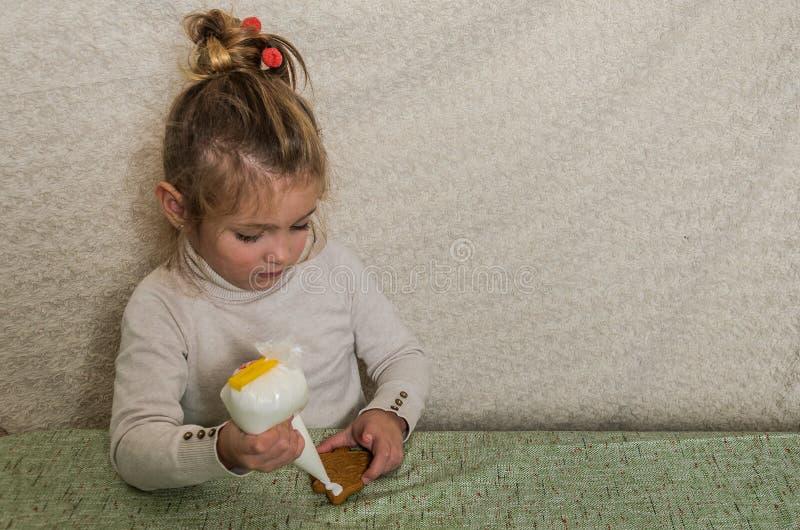 Mała powabna dziewczyna dekoruje nowego roku miodownika z białego cukieru lodowaceniem fotografia stock