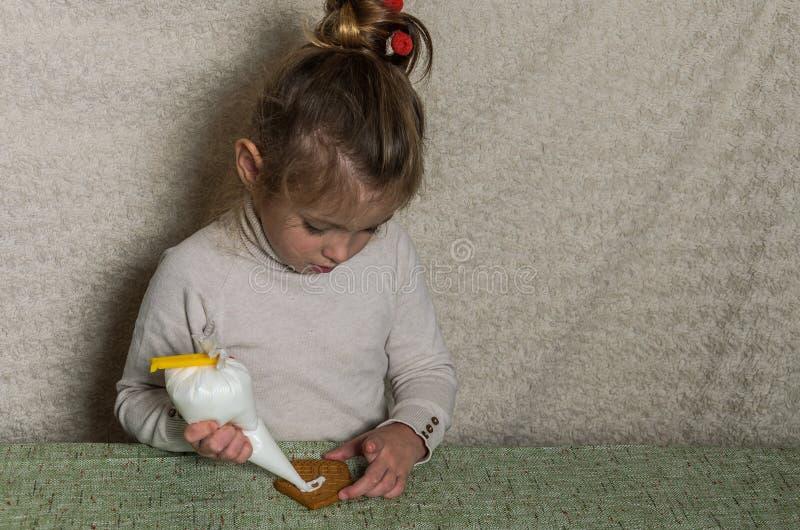 Mała powabna dziewczyna dekoruje nowego roku miodownika z białego cukieru lodowaceniem zdjęcie royalty free