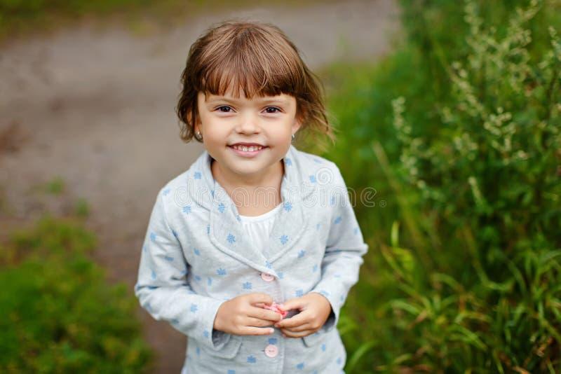 Mała powabna dziewczyna z brązem ono przygląda się na tle lato obrazy stock
