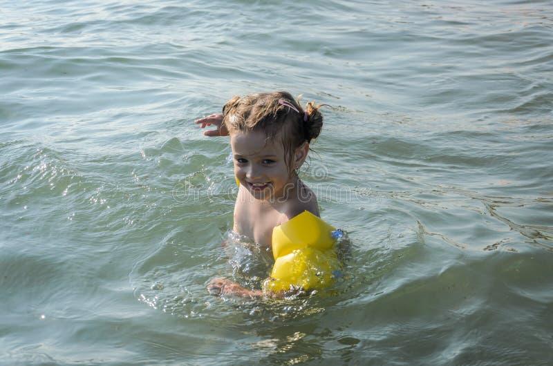 Mała powabna dziewczynka kąpać szczęśliwego w morzu z lifebuoys na jej rękach fotografia stock