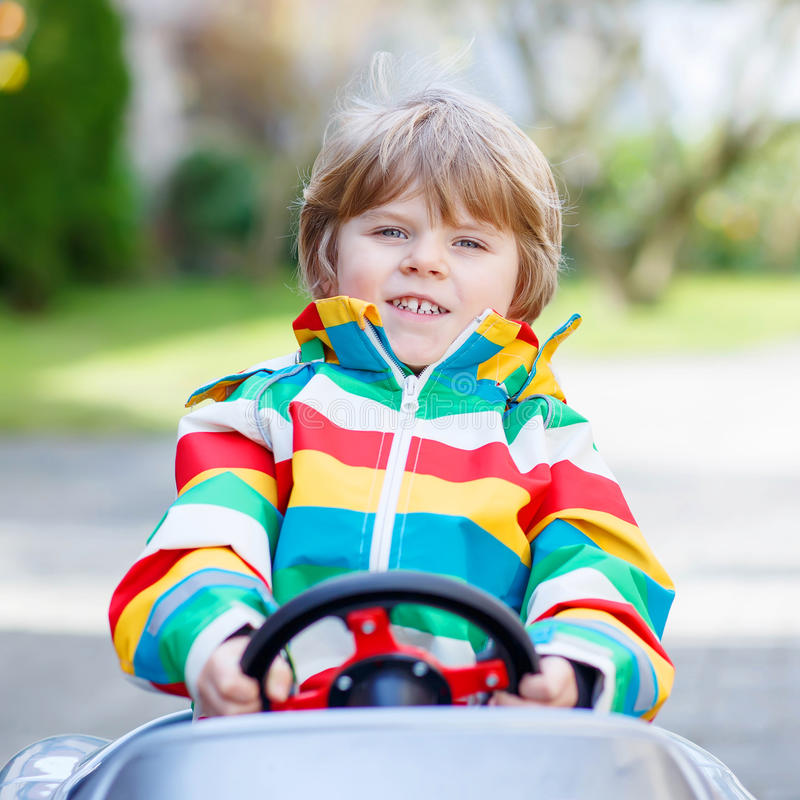 Mała preschool chłopiec jedzie dużego zabawkarskiego starego rocznika samochód, outdoors zdjęcia royalty free