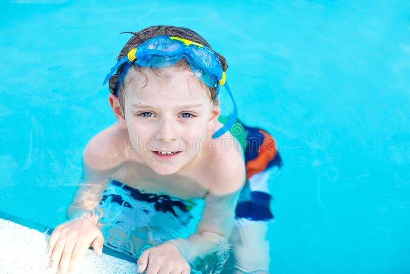 Mała preschool dzieciak chłopiec robi pływaniu turniejowemu sportowi Dzieciak dosięga krawędź basen z pływackimi gogle kochanie obrazy royalty free