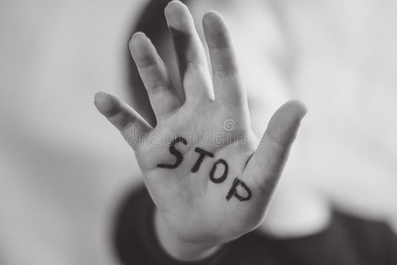 Mała przelękła dziewczyna pokazuje słowo «przerwa «pisać na ręce Dzieci poddają przemoc i publikować w domu i fotografia stock