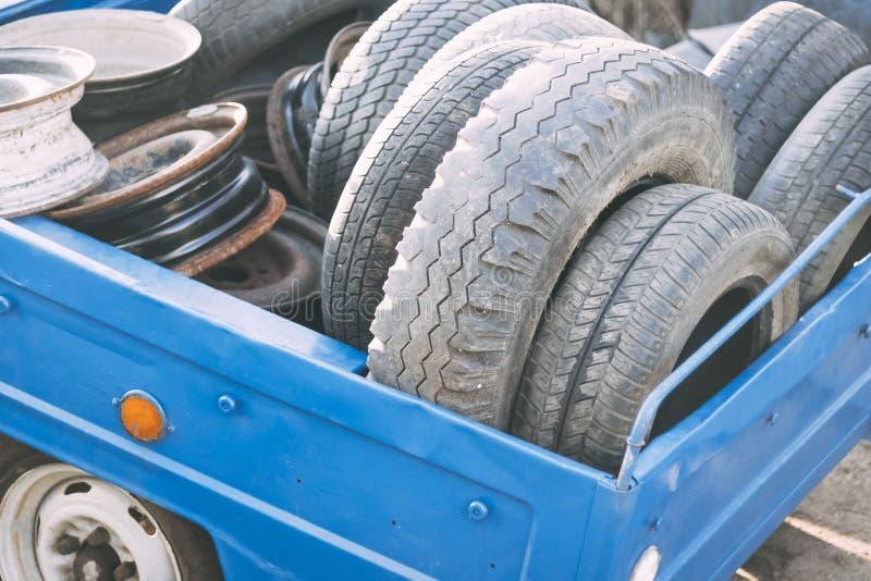 mała przyczepa, błękitny kolor ja zawiera mnóstwo starych koła i opony pojęcie zmiany opony na samochodzie fotografia royalty free