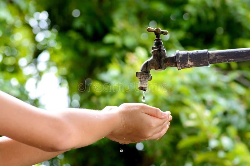 Mała ręka czekać na wodną kroplę od faucet obraz stock