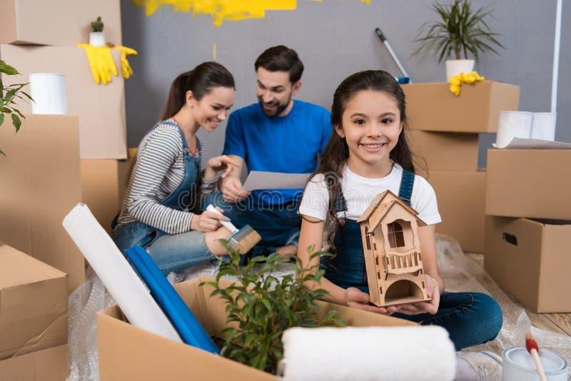 Mała radosna dziewczyna bawić się z drewno miniatury domem podczas gdy rodzice robią naprawom obrazy stock