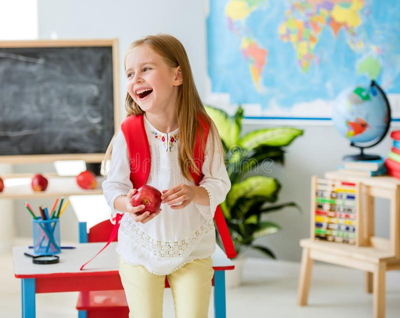 Mała roześmiana blond dziewczyna trzyma jabłka w szkolnej sali lekcyjnej obrazy stock