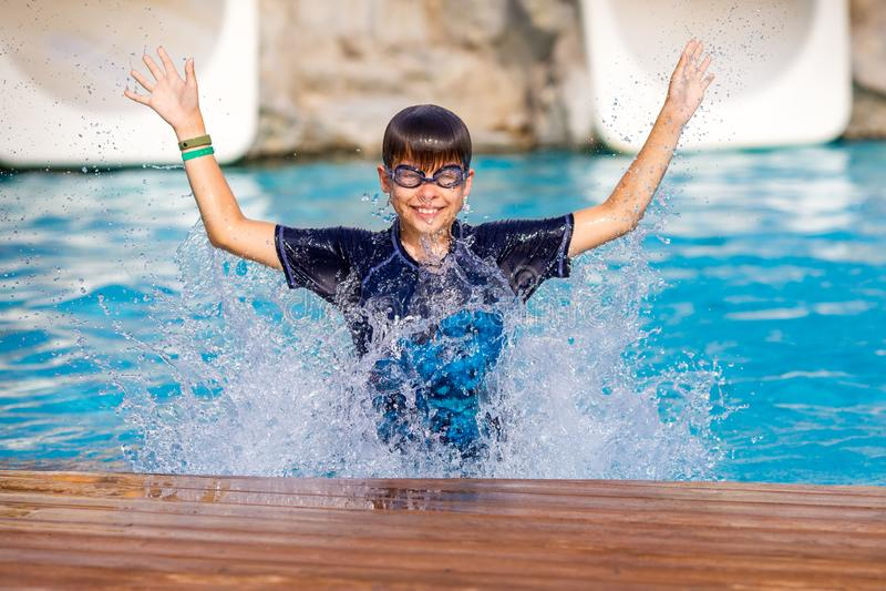 Mała rozochocona chłopiec skacze basen i robi wodnemu pluśnięciu, cieszy się czas w odświeżającej wodzie fotografia stock