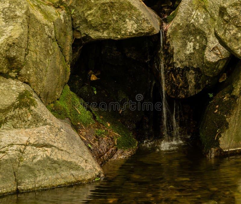 Mała siklawa płynie nad wielkimi kamieniami zdjęcie royalty free