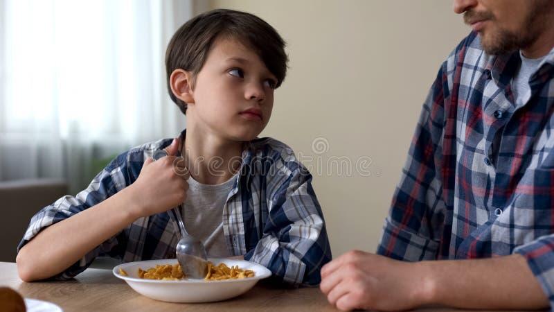 Mała smutna chłopiec miesza cornflakes z łyżką, patrzeje ojca, biedny apetyt zdjęcie royalty free
