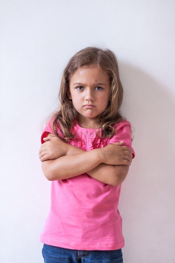 Mała Smutna dziewczyna Z Wyrażeniową twarzą Wewnątrz Na biel ściany tle obraz stock