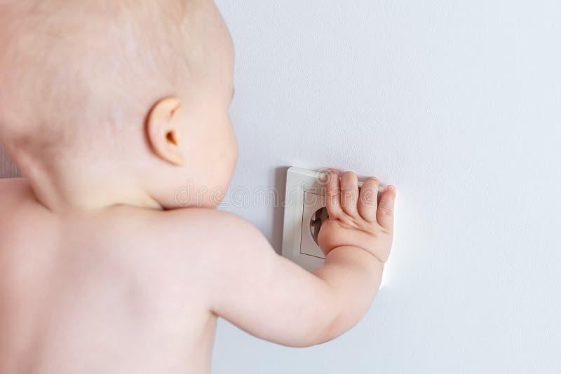 Mała sowizdrzalska berbeć chłopiec bawić się stawiać palce w władzy elektrycznej nasadce w biel ścianie przy domem i próbuje Dzie zdjęcia stock