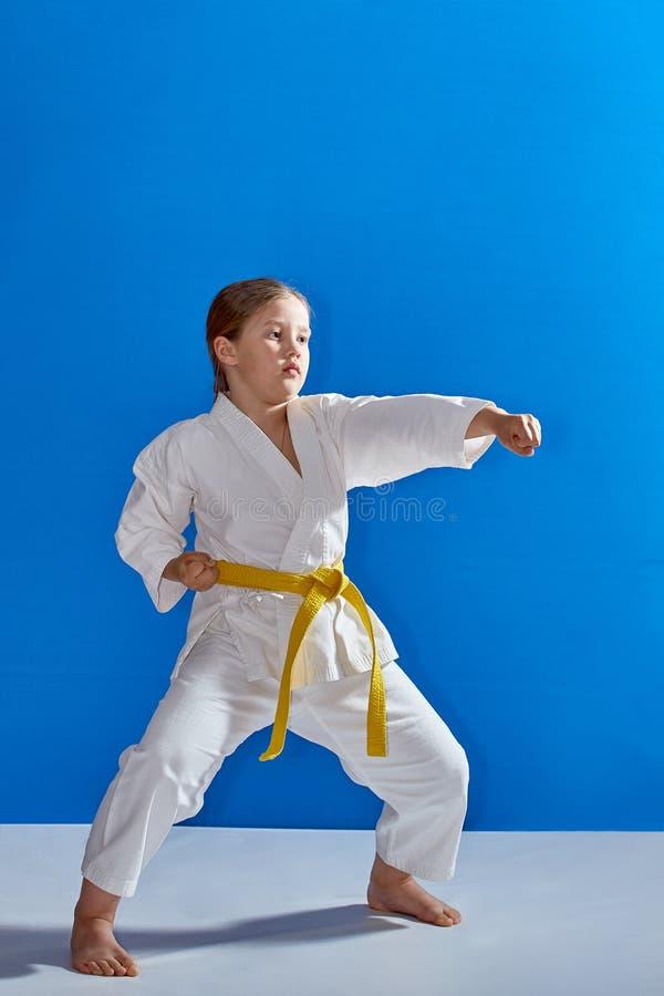 Mała sportsmenka bije cios rękę w stojaku karate zdjęcie stock