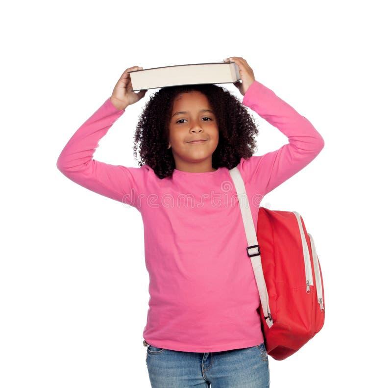 Mała studencka dziewczyna z książką na jej głowie obrazy royalty free