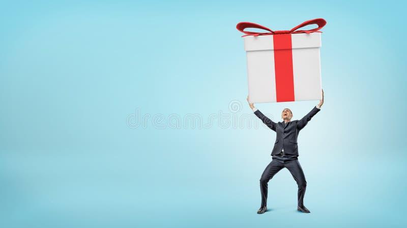 Mała szczęśliwa biznesmen pozycja na błękitnym mieniu i tle gigantyczny prezenta pudełko z oba rękami zdjęcie stock