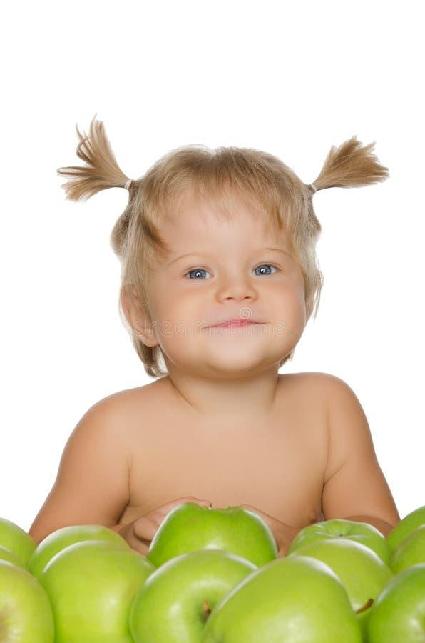 Mała szczęśliwa dziewczyna z zielonymi jabłkami zdjęcia royalty free