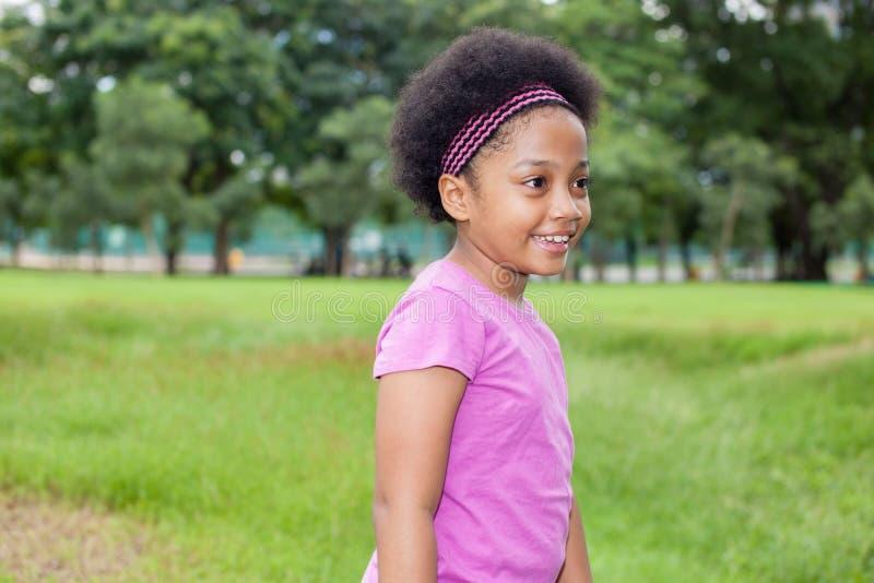 Mała szczęśliwa i radosna amerykanin afrykańskiego pochodzenia dziewczyna bawić się w parku zdjęcia royalty free