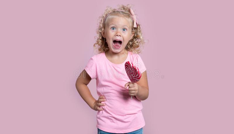 Mała szczęśliwa krzycząca blond dziewczyna z lizakiem candyisolated nad menchiami fotografia stock