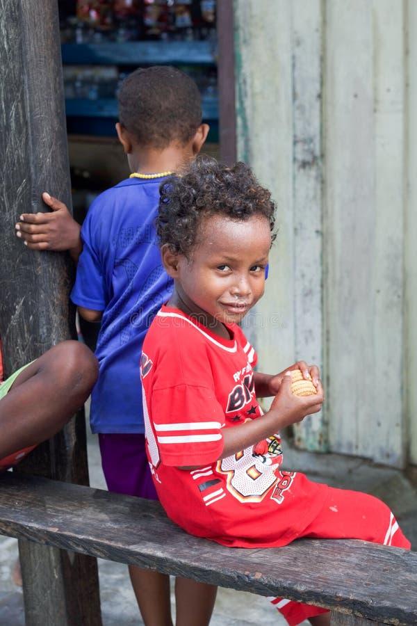 Mała szczęśliwa miejscowa chłopiec z ciastkami w jego rękach zdjęcia royalty free