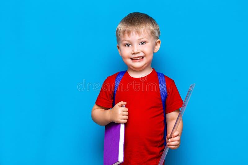 Mała szczęśliwa uśmiechnięta chłopiec z szkłami na jego głowa, książka w rękach, schoolbag na jego brać na swoje barki tylna szko zdjęcie royalty free