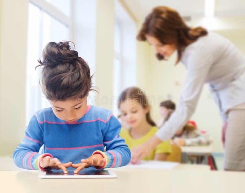 Mała szkolna dziewczyna z pastylka komputerem osobistym nad sala lekcyjną fotografia royalty free