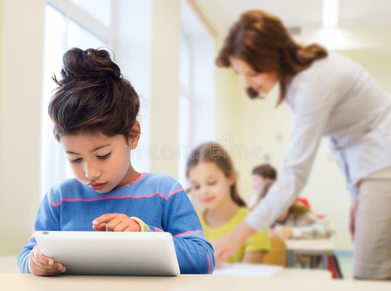 Mała szkolna dziewczyna z pastylka komputerem osobistym nad sala lekcyjną obraz royalty free