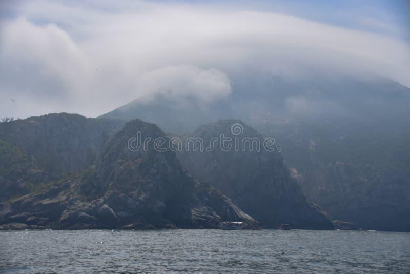 Mała tajemnicy wyspa w mgle z chmurami obraz stock