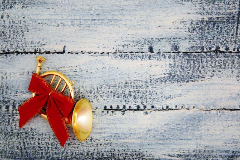 Mała trąbka, róg z czerwonym łękiem na przetartym błękitnym drewnianym tle dekoracje świąteczne ekologicznego drewna zdjęcie royalty free