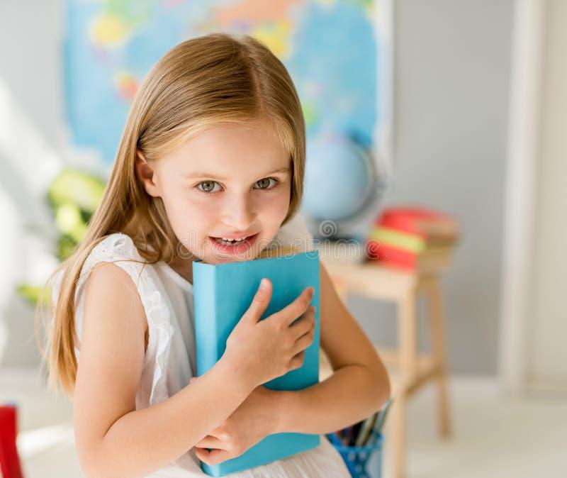Mała uśmiechnięta blond dziewczyna trzyma błękitną książkę w szkolnej klasie zdjęcia royalty free