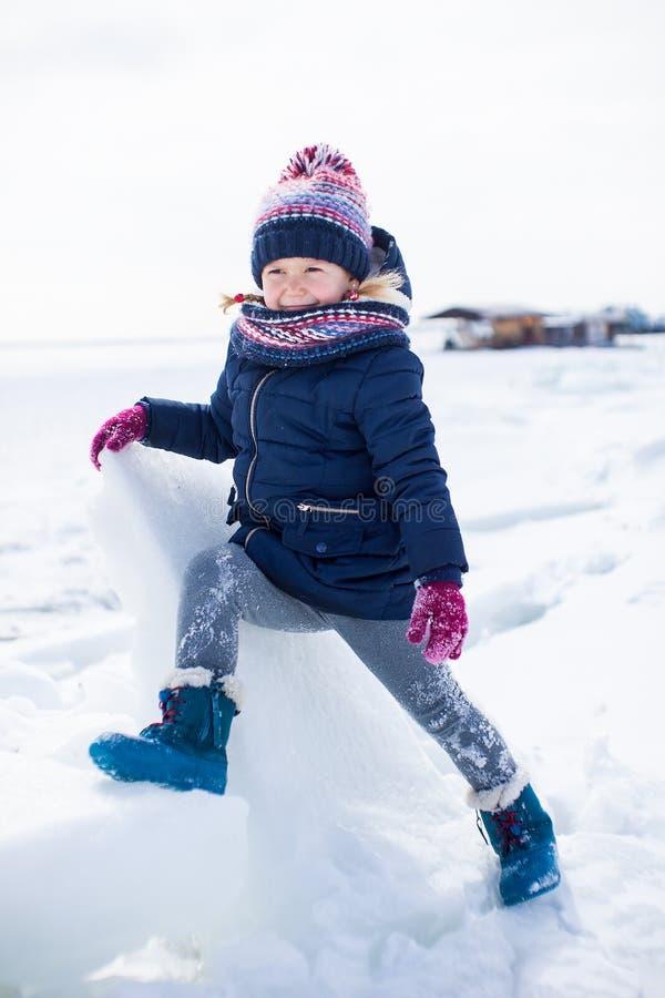 Mała uśmiechnięta dziewczyna w zim płótnach z lodem wokoło i śniegiem obrazy royalty free