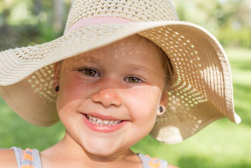 Mała uśmiechnięta dziewczyna z Plażowym kapeluszem fotografia stock
