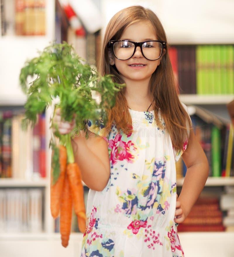 Mała uśmiechnięta dziewczyna z wiązką organicznie marchewki obraz royalty free