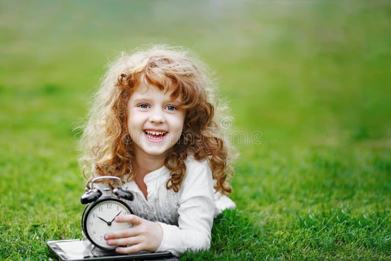 Mała uczennica odpoczywa na gazonie w jesień parku fotografia royalty free